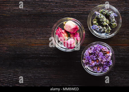 Bowls of Dried Lavender, Rose, and Sea Lavender on Dark Table with Space for Copy - Stock Photo