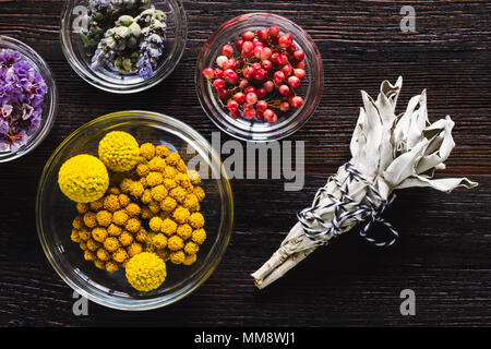 White Sage Smudge with Bowls of Dried Flowers on Dark Table - Stock Photo