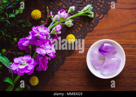 Bowl of Amethyst Crystals on Teak Table with Flowers - Stock Photo