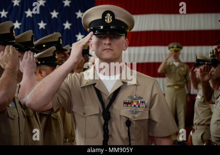 PORTLAND, Ore. (Sept. 16, 2017) Newly frocked Chief Boatswain's Mate Damian Carrell, assigned to the submarine tender USS Frank Cable (AS 40), salutes sideboys during a chief petty officer pinning ceremony at the Navy Operational Support Center in Portland, Ore., Sept. 16. Frank Cable, currently in Portland for a scheduled dry-dock phase maintenance availability, conducts maintenance and support of submarines and surface vessels in the Indo-Asia-Pacific region. (U.S. Navy photo by Mass Communication Specialist Seaman Heather C. Wamsley/Released) - Stock Photo