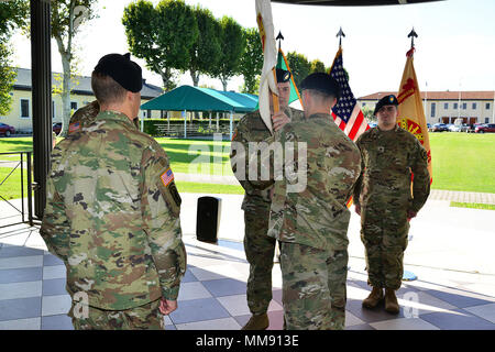 1st Sgt. Brad J. Lowrance, center, passes the guidon to Capt. Brennan T. Roorda, right, outgoing commander, during a change of command ceremony for U.S. Army Garrison Italy Headquarters Company at  Caserma Ederle in Vicenza, Italy, Sept. 18, 2017.  (U.S. Army photo by Visual Information Specialist Antonio Bedin/released) - Stock Photo