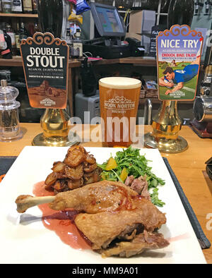 Bar food, duck leg, orange sauce, with beer pumps on a bar, in a traditional English pub, England, UK - Stock Photo
