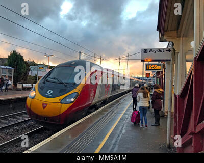 Virgin Pendolino arrives at Motherwell Railway Station, North Lanarkshire, Scotland at dusk, UK - Stock Photo