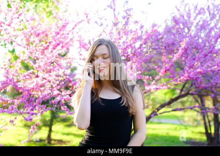 Smiling girl walking in spring park and talking by smartphone. - Stock Photo