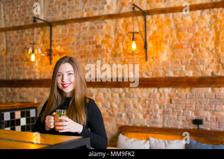 Satisfied girl sitting near wooden table with cup of lemonade in cafe and relaxing. - Stock Photo