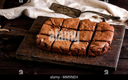 baked rectangular chocolate brownie pie is cut into squares on a brown kitchen cutting board, top view - Stock Photo