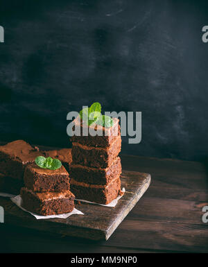two stacks of square pieces of chocolate baked brownie pie on a brown wooden board, vintage toning, copy space - Stock Photo