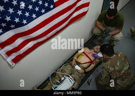 U.S. Air Force Col. Dai Tran, Medical Officer with the 407th Air Expeditionary Group is checking the heartbeat of Senior Airman Robert Daniels, a simulated patient during training in the Middle East, Sept 14, 2017. Service members participated in a mass casualty exercise to increase proficiency and preparedness in an emergency situation. - Stock Photo