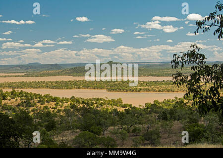 Spectacular landscape with wooded islands rising from waters of immense lake formed by Burdekin Falls dam & hemmed by trees under blue sky, Australia - Stock Photo