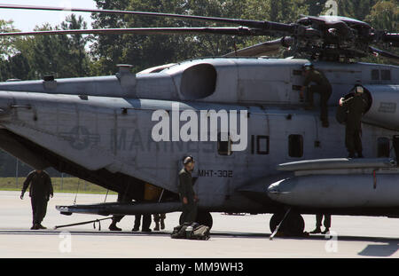 Marines assigned to Marine Heavy Helicopter Training Squadron 302 perform after flight inspections on a CH-53E Super Stallion at Marine Corps Air Station New River, N.C., Sept. 22, 2017. HMHT-302 celebrated the end of the 2017 fiscal year by flying eight helicopters in formation over their squadron. HMHT-302 is assigned to Marine Aircraft Group 29, 2nd Marine Aircraft Wing. (U.S. Marine Corps photo by Lance Cpl. Justin Roux/ Released) - Stock Photo