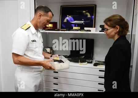 170925-N-FJ200-028 WASHINGTON (Sept. 25, 2018) Chief of Naval Operations Adm. John Richardson inspects a .38 M1889 Colt Navy revolver recovered from the wreck of the USS Maine (ACR-1) while learning of its historical importance from Museum Specialist Jennie Ashton, during a tour of the armory spaces of Naval History and Heritage Command. The sinking of USS Maine and loss of 266 Sailors in Havana Harbor, Cuba, on February 15, 1898, served as a catalyst for the Spanish-American War. (U.S. Navy photo by Mass Communication Specialist 1st Class Clifford L. H. Davis/Released) - Stock Photo