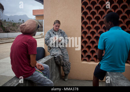 U.S. Air Force Maj. Lisa Ray, a public affairs officer with Joint Task Force - Leeward Islands, interviews U.S. citizens David Shargel and Naya Shargel at Douglas-Charles Airport in Melville Hall, Dominica, Sept. 26, 2017. Naya was separated from his father during Hurricane Maria; the two were reunited after a three-day search by U.S. service members with JTF-LI. At the request of the Department of State, JTF-LI has deployed aircraft and service members to assist in the voluntary evacuation of U.S. citizens from Dominica. The task force is a U.S. military unit composed of Marines, Soldiers, Sa - Stock Photo
