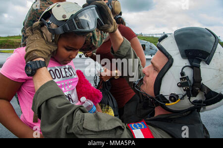 170928-N-NM806-0010  DOMINICA (Sept. 28, 2017) Naval Aircrewman (Helicopter) 2nd Class Nicholas Glass, assigned to Helicopter Sea Combat Squadron (HSC) 22 aboard to the amphibious assault ship USS Wasp (LHD 1), prepares a child for evacuation following the landfall of Hurricane Maria. Dominica residents are being evacuated to local airports and then to the nearby islands of Martinique and Guadalupe. The Department of Defense is supporting the United States Agency for International Development (USAID), the lead federal agency, in helping those affected by Hurricane Maria to minimize suffering a - Stock Photo
