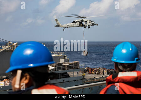 170928-N-AY374-134  CARIBBEAN SEA (Sept. 28, 2017) Sailors aboard the amphibious assault ship USS Kearsarge (LHD 3) observe as an MH-60 Sea Hawk helicopter transfers pallets of supplies from the fast combat support ship USNS Supply (T-AOE 6) during replenishment-at-sea for continuing operations in Puerto Rico. Kearsarge is assisting with relief efforts in the aftermath of Hurricane Maria. The Department of Defense is supporting the Federal Emergency Management Agency, the lead federal agency, in helping those affected by Hurricane Maria to minimize suffering and is one component of the overall - Stock Photo