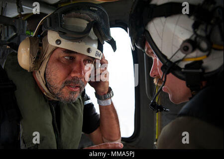 170929-N-VK310-0051  CARIBBEAN SEA (Sept. 29, 2017) Thierry Rolle, a resident of French Guadalupe, speaks with Naval Aircrewman (Helicopter) 2nd Class Brandon Larnard on an MH-60S Sea Hawk helicopter attached to Helicopter Sea Combat Squadron (HSC) 22 prior to departing the amphibious assault ship USS Wasp (LHD 1) en route to the island of Guadalupe.  Rolle and another passenger were rescued by HSC-22 personnel after their private aircraft crashed into the water off the coast of Dominica on Sept. 28. Wasp is currently participating in humanitarian relief efforts in the Caribbean Sea following  - Stock Photo