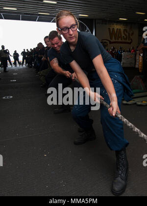 170926-N-BD308-0031  CARIBBEAN SEA (Sept. 26, 2017) Sailors assigned to the amphibious assault ship USS Wasp (LHD 1) heave around a line in the hangar bay during a replenishment-at-sea. Wasp is off the coast of the island of Dominica providing aid to evacuees as part of first response efforts in wake of Hurricane Maria. The Department of Defense is supporting the United States Agency for International Development (USAID), the lead federal agency, in helping those affected by Hurricane Maria to minimize suffering and is one component of the overall whole-of-government response effort.(U.S. Navy - Stock Photo