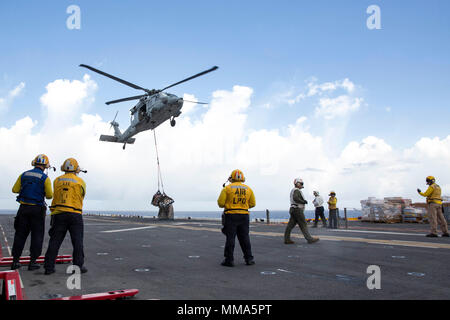 170928-N-KW492-245  CARIBBEAN SEA (Sept. 28, 2017) Sailors aboard the amphibious assault ship USS Kearsarge (LHD 3) observe as an MH-60 Sea Hawk helicopter drops pallets of supplies onto the flight deck during a replenishment-at-sea with the fast combat support ship USNS Supply (T-AOE 6) for continuing operations in Puerto Rico. Kearsarge is assisting with relief efforts in the aftermath of Hurricane Maria. The Department of Defense is supporting the Federal Emergency Management Agency, the lead federal agency, in helping those affected by Hurricane Maria to minimize suffering and is one compo - Stock Photo