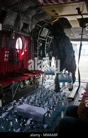 U.S. Army Sgt. Delton Reynolds, a helicopter crew chief with Joint Task Force - Leeward Islands, loads water onto a CH-47 Chinook helicopter at the Pointe-à-Pitre International Airport in Pointe-à-Pitre, Guadeloupe, Sept. 29, 2017. The helicopter delivered water to be distributed to people in need at the Douglas-Charles Airport in Melville Hall, Dominica. At the request of partner nations and both the Department of State and the U.S. Agency for International Development, JTF-LI has deployed aircraft and service members to areas in the eastern Caribbean Sea affected by hurricanes Irma and Maria - Stock Photo