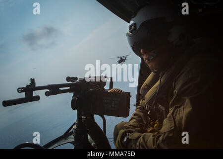 A crew chief with Marine Light Attack Helicopter Squadron 169 observes the ocean while sitting in a UH-1Y Venom over Okinawa, Japan, September 28, 2017. The squadron conducted aerial live-fire training in Okinawa, which is crucial to maintaining a stronger, more capable, forward deployed force in the Indo-Asia-Pacific region. The aircraft is assigned to HMLA-169, Marine Aircraft Group 39, 3rd Marine Aircraft Wing, currently forward deployed under the unit deployment program with MAG-36, 1st MAW. (U.S. Marine Corps photo by Lance Cpl. Andy Martinez) - Stock Photo