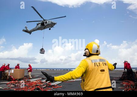 170928-N-KW492-303 CARIBBEAN SEA (Sept. 28, 2017) Aviation Boatswain's Mate (Handling) 2nd Class Fernando Hinostroza directs an MH-60S Sea Hawk as it drops supplies transferred from the fast combat support ship USNS Supply (T-AOE 6) onto the flight deck of the amphibious assault ship USS Kearsarge (LHD 3) during a replenishment-at-sea for continuing operations in Puerto Rico. Kearsarge is assisting with relief efforts in the aftermath of Hurricane Maria. The Department of Defense is supporting FEMA, the lead federal agency, in helping those affected by Hurricane Maria to minimize suffering and - Stock Photo