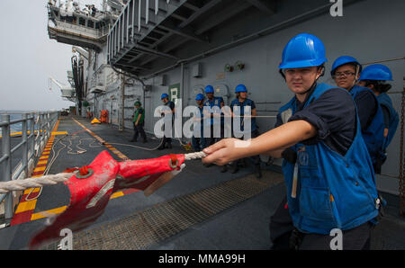 170926-N-BD308-0299 Caribbean Sea (Sept. 26, 2017) Sailors assigned to the amphibious assault ship USS Wasp (LHD 1) heave around a line during a replenishment-at-sea with the fast combat support ship USNS Supply (T-AOE-6). Wasp is off the coast of the island of Dominica providing aid to evacuees as part of first response efforts in wake of Hurricane Maria. (U.S. Navy photo by Mass Communication Specialist 3rd Class Levingston Lewis/Released) - Stock Photo