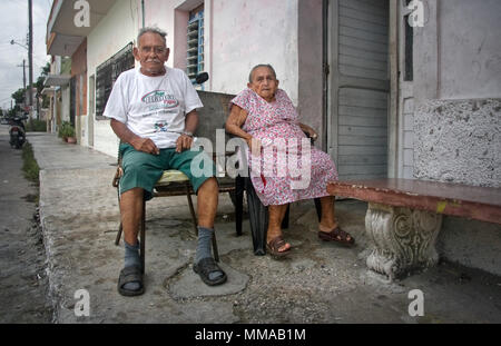 Progreso, Mexico - October 14, 2007: Old couple of Progreso residents sitting on their porch on a hot evening with tired expression in their face. - Stock Photo