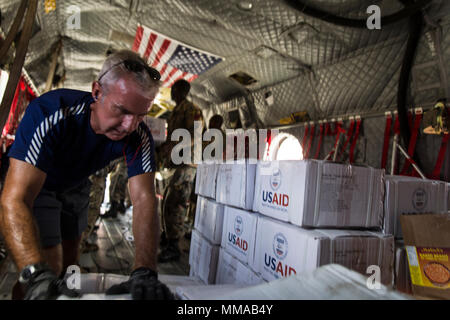 A volunteer loads relief supplies on a U.S. Army CH-47 Chinook helicopter at the port of Roseau, Dominica, Oct. 3, 2017. The aircraft delivered rice and kitchen sets from the U.S. Agency for International Development to the community of Wotten Waven, Dominica. At the request of USAID, JTF-LI has deployed aircraft and service members to assist in delivering relief supplies to Dominica in the aftermath of Hurricane Maria. The task force is a U.S. military unit composed of Marines, Soldiers, Sailors and Airmen, and represents U.S. Southern Command's primary response to the hurricanes that have af - Stock Photo