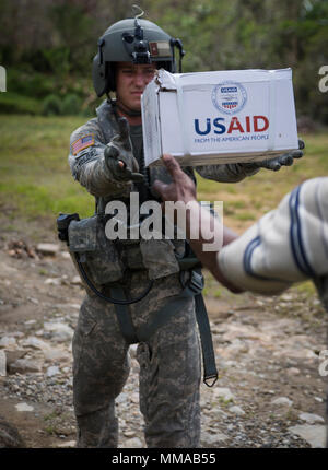 U.S. Army Sgt. Delton Reynolds, a flight engineer, passes humanitarian aid to a Domincan citizen at Wotten Waven, Dominica, Oct. 3, 2017. The aircraft picked up bags of rice and kitchen sets from the U.S. Agency for International Development for delivery to the community. The service members of JTF-LI are supporting the delivery of humanitarian assistance to the island of Dominica in the wake of Hurricane Maria. At the request of partner nations and both the Department of State and USAID, JTF-LI has deployed aircraft and service members to areas in the eastern Caribbean Sea affected by hurrica - Stock Photo