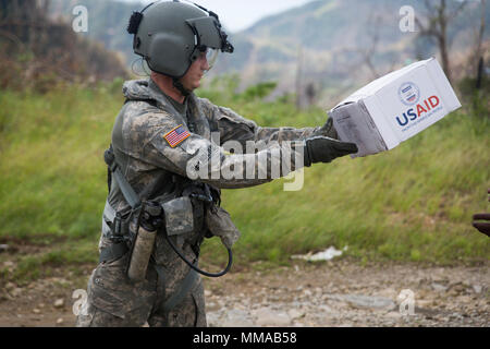 U.S. Army Sgt. Delton Reynolds, a flight engineer with Joint Task Force - Leeward Islands, passes humanitarian aid to a local resident at Wotten Waven, Dominica, Oct. 3, 2017. The aircraft delivered rice and kitchen sets from the U.S. Agency for International Development to the community. At the request of USAID, JTF-LI has deployed aircraft and service members to assist in delivering relief supplies to Dominica in the aftermath of Hurricane Maria. The task force is a U.S. military unit composed of Marines, Soldiers, Sailors and Airmen, and represents U.S. Southern Command's primary response t - Stock Photo