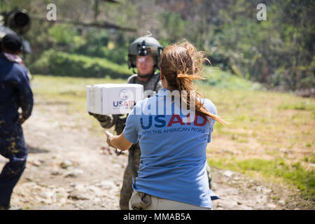 Viktoria Martin, the civil-military liaison coordinator with the U.S. Agency for International Development, and U.S. Army Sgt. Delton Reynolds, a flight engineer with Joint Task Force - Leeward Islands, pass out kitchen sets in Wotten Waven, Dominica, Oct. 3, 2017. At the request of USAID, JTF-LI has deployed aircraft and service members to assist in delivering relief supplies to Dominica in the aftermath of Hurricane Maria. The task force is a U.S. military unit composed of Marines, Soldiers, Sailors and Airmen, and represents U.S. Southern Command's primary response to the hurricanes that ha - Stock Photo