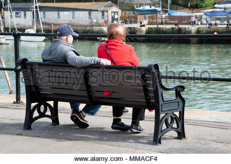 Image from behind of an older couple sitting looking across the Harbour, Weymouth,  Dorset, England, UK - Stock Photo