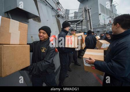 170927-N-UB406-139 IRISH SEA (Sept. 27, 2017) Sailors assigned to the Arleigh Burke-class guided-missile destroyer USS Mitscher (DDG 57) participate in a working party during a replenishment-at-sea with the Lewis and Clark-class dry cargo ship USNS Medgar Evers (T-AKE 13). Mitscher is conducting naval operations in the U.S. 6th Fleet area of operations in support of U.S. national security interests in Europe. (U.S. Navy photo by Mass Communication Specialist Seaman Cameron M. Stoner/Released) - Stock Photo