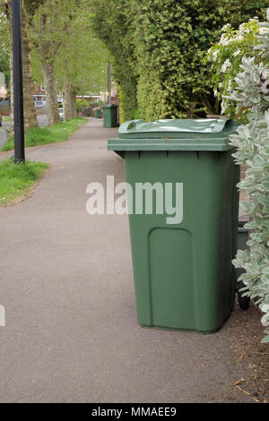May 2018 - Green garden waste recycling bins on a leafy suburban street in Portishead, North Somerset. Near Bristol, England. - Stock Photo