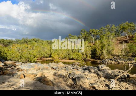 Black clouds and rainbow over bushland in Palmer River Goldfield, Far North Queensland, FNQ, QLD, Australia