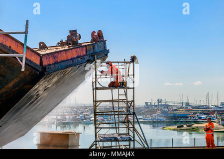 Man jet washing a ship in preparation for repairs - Stock Photo