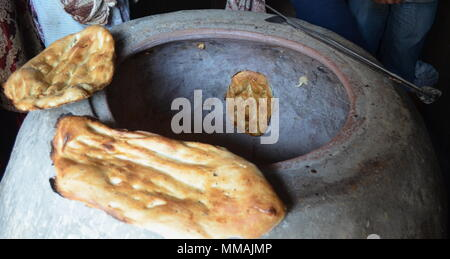 Traditional Azerbaijan way of baking lavash bread in an oven - Stock Photo