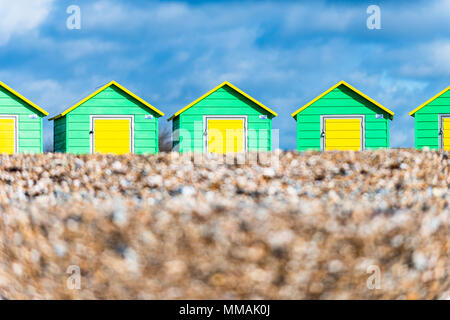 A row of coloured beach huts on the pebble beach at Littlehampton in West Sussex, England. - Stock Photo
