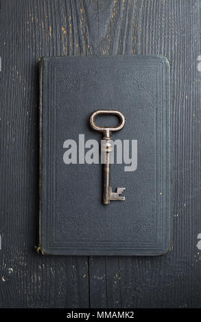 Vintage Key over black leather book cover and wooden table, top view - Stock Photo