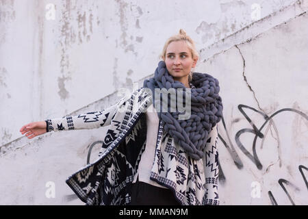 Blonde young beautiful fashion girl wearing aztec black and white jacket and knitted grey vest scarf. Festival outfit. Lifestyle street fashion trend - Stock Photo
