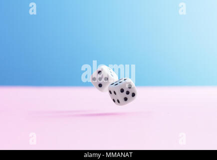 Two dice fall over pink background - Stock Photo