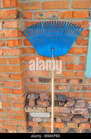 Blue plastic rake for harvesting leaves and grass are near the red brick wall - Stock Photo