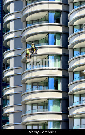London,England, UK. Maintenance workeers abseiling down the building'The Corniche' apartments on Albert Embankment, Vauxhall - Stock Photo