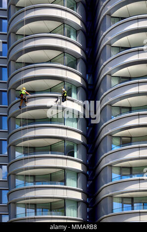 London,England, UK. Maintenance workers abseiling down the building 'The Corniche' apartments on Albert Embankment, Vauxhall - Stock Photo