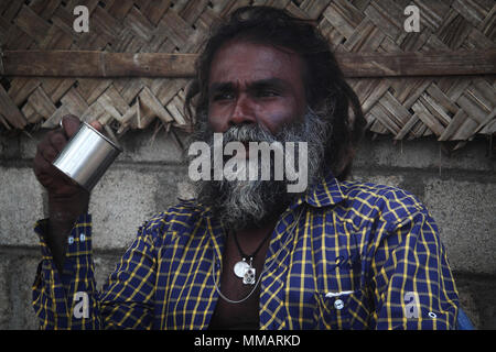Tamil man drinking tea from metal cup near his house - Stock Photo