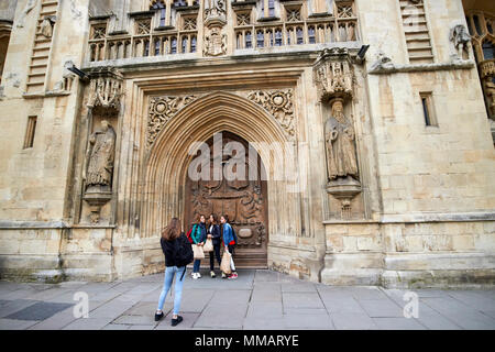 female students pose in front of large carved west front door of Bath Abbey Bath England UK - Stock Photo