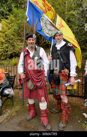 Two men dressed in traditional Scottish garb and carrying Scottish flags at an independence rally and march in Glasgow, Scotland, UK - Stock Photo