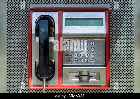 Old red telephone booth in box outdoor in city street. Close up, retro and vintage. - Stock Photo