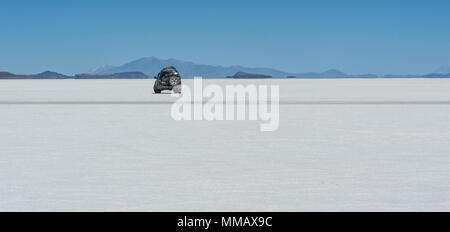 Off-road car in the Salar de Uyuni. It  is largest salt flat in the World (UNESCO World Heritage Site) - Altiplano, Bolivia, South America - Stock Photo