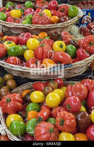 a selection or variety of different and colourful tomatoes displayed for sale on a greengrocers stall at borough market in london. tomato varieties. - Stock Photo