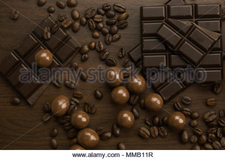Assorted milk and dark chocolate with coffee beans scattered on a dark brown surface in a full frame close up background from above - Stock Photo